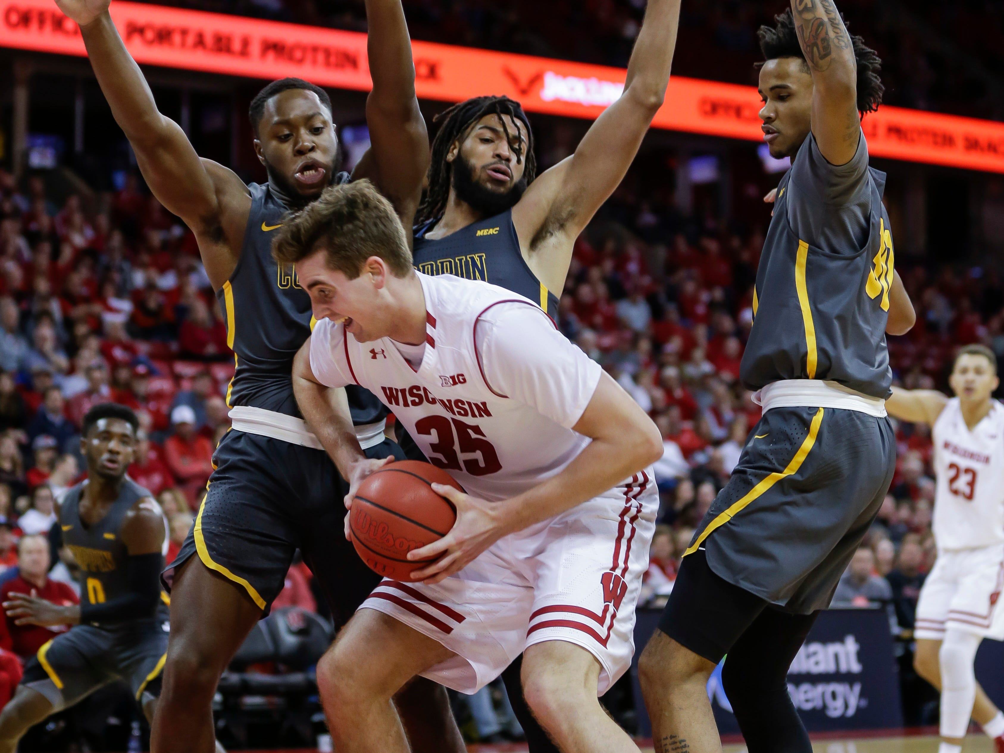 Wisconsin's Nate Reuvers works against Coppin State's Nigel Marshall, left, Chad Andrews-Fulton and Jordan Hardwick.