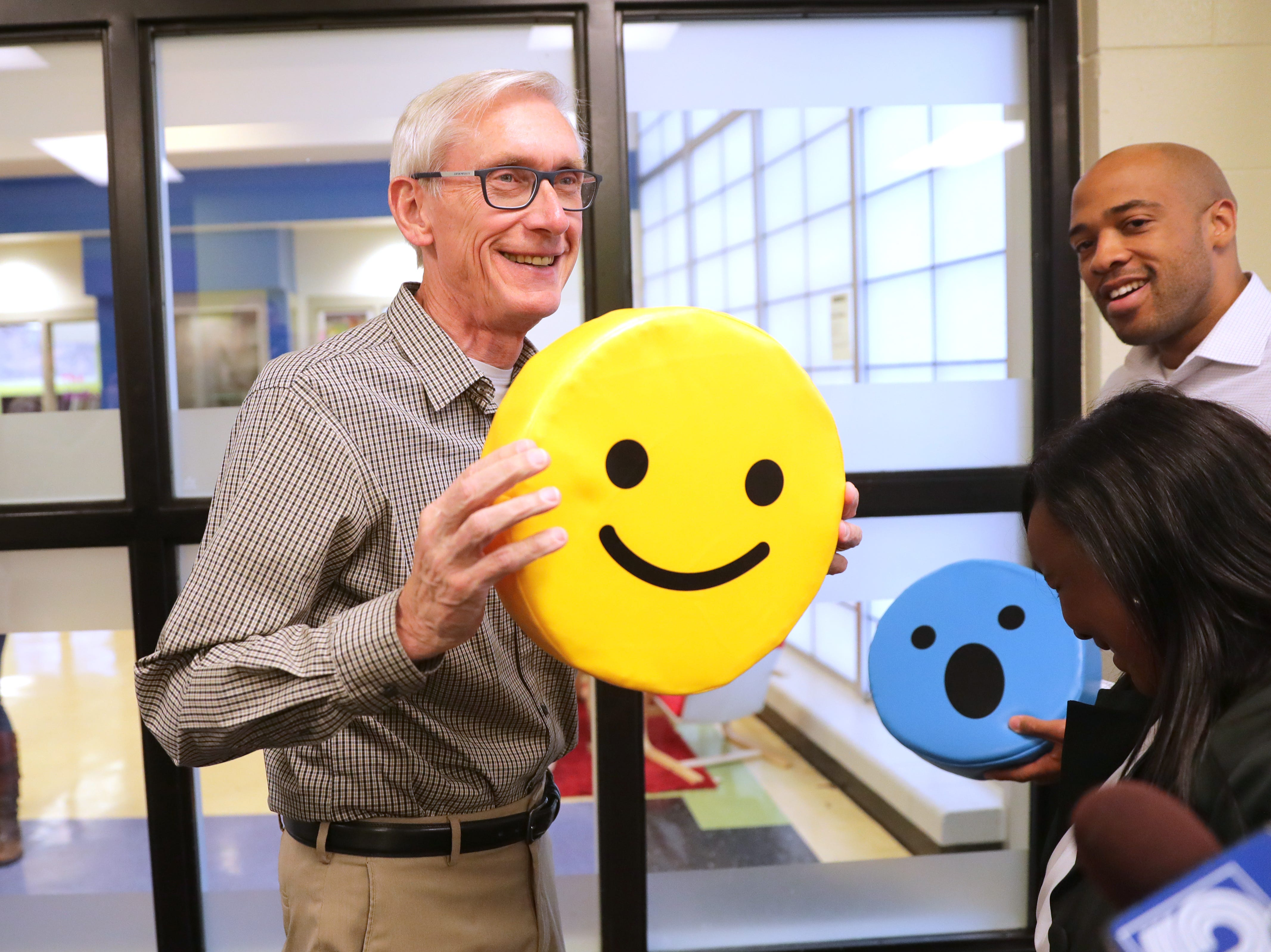 Gov.-elect Tony Evers jokingly hold a smiley emoji pillow to reflect how he's feeling after winning the election as he and Lt. Gov.-elect Mandela Barnes visited the Boys & Girls Club of Dane County in Madison after they were elected Tuesday.
