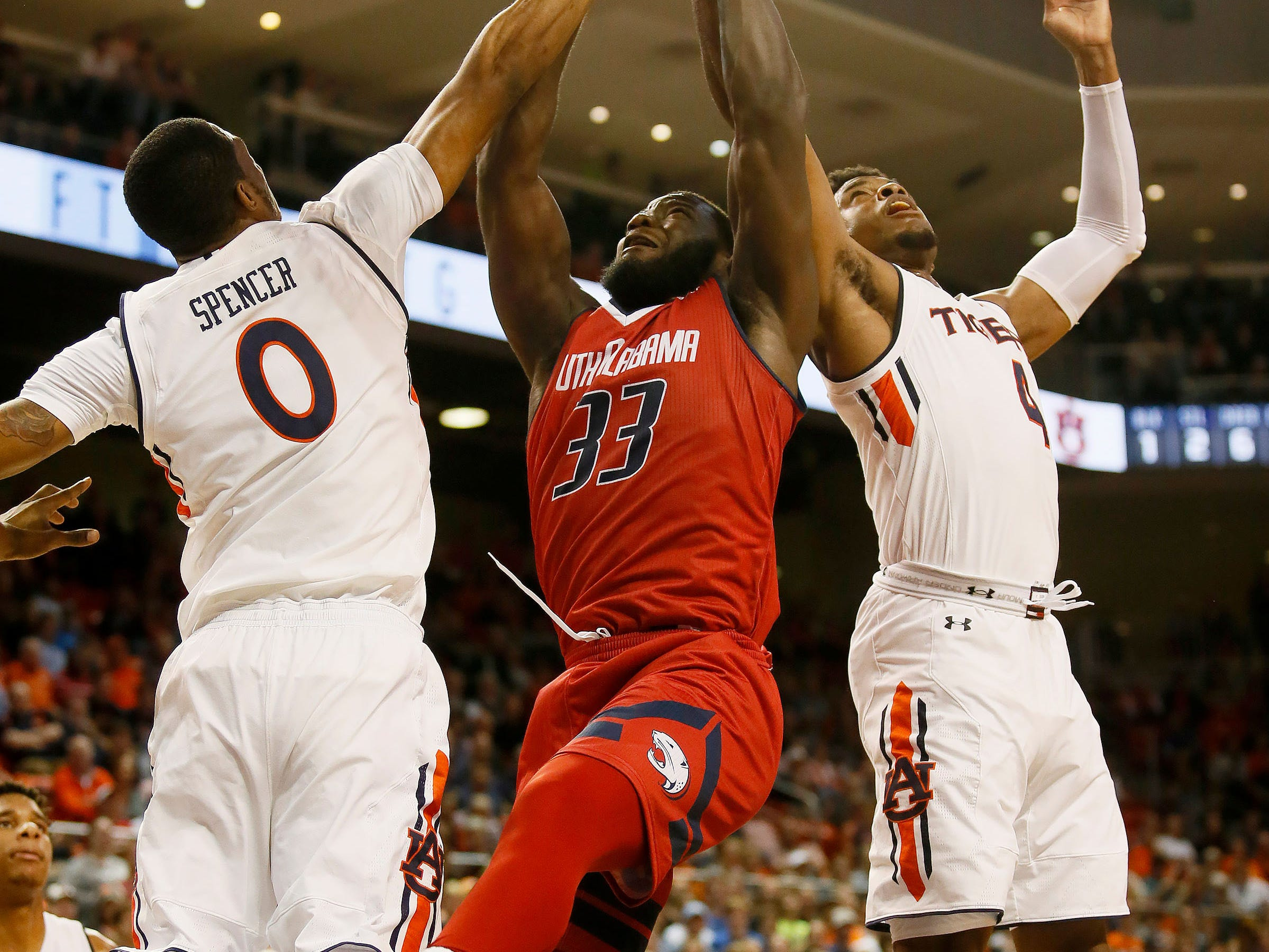 Nov 6, 2018; Auburn, AL, USA; South Alabama Jaguars forward Josh Ajayi (33) fights for a rebound with Auburn Tigers forward Horace Spencer (0) and guard Malik Dunbar (4) during the first half at Auburn Arena. Mandatory Credit: John Reed-USA TODAY Sports