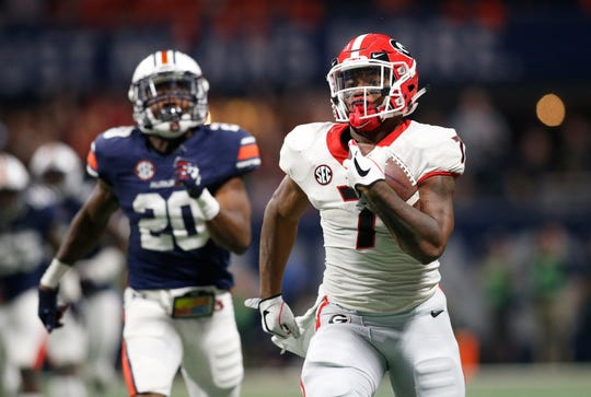 Georgia running back D'Andre Swift (7) runs for a touchdown as Auburn defensive back Jeremiah Dinson (20) chases during SEC Championship game at Mercedes-Benz Stadium on Dec. 2, 2017, in Atlanta.