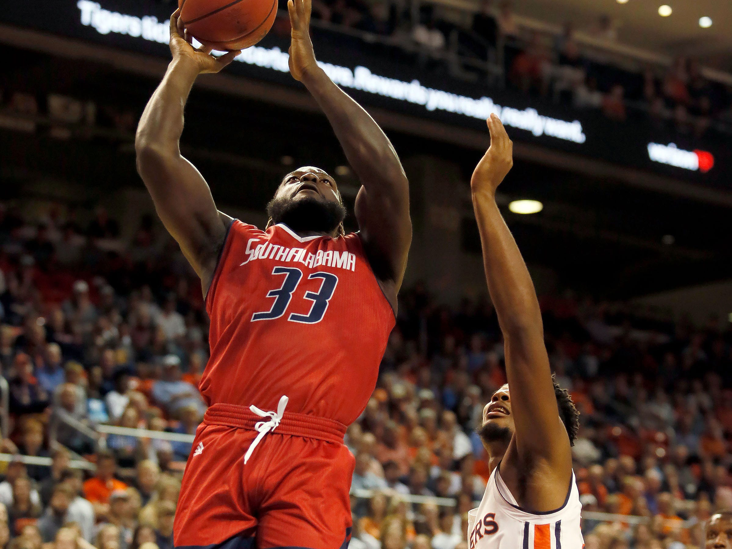 Nov 6, 2018; Auburn, AL, USA; South Alabama Jaguars forward Josh Ajayi (33) takes a shot over Auburn Tigers forward Anfernee McLemore (24) during the first half at Auburn Arena. Mandatory Credit: John Reed-USA TODAY Sports