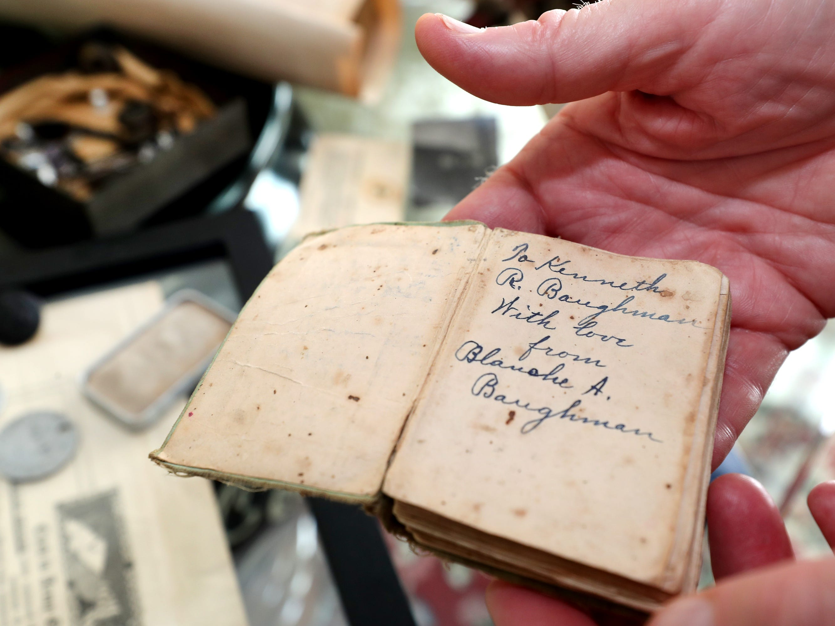 Steve Baughman show off a prayer book that his grandfather Kenneth Baughman carried during World War II,  on Monday, Nov. 5, 2018.