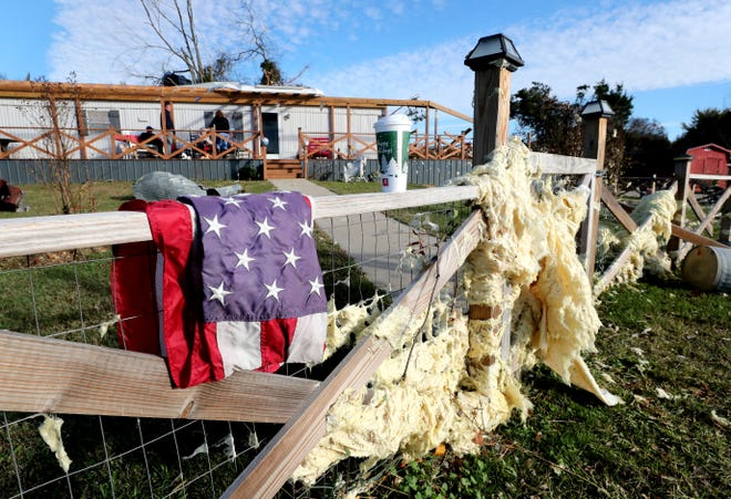 Insulation sticks in a fence line in front of a mobile home along Rock Springs Midland Road in Christiana, Tenn., on Tuesday, Nov. 6, 2018, after a tornado that morning. The flag was left intact on a pole that was knocked down in the yard and was later placed on the fence.