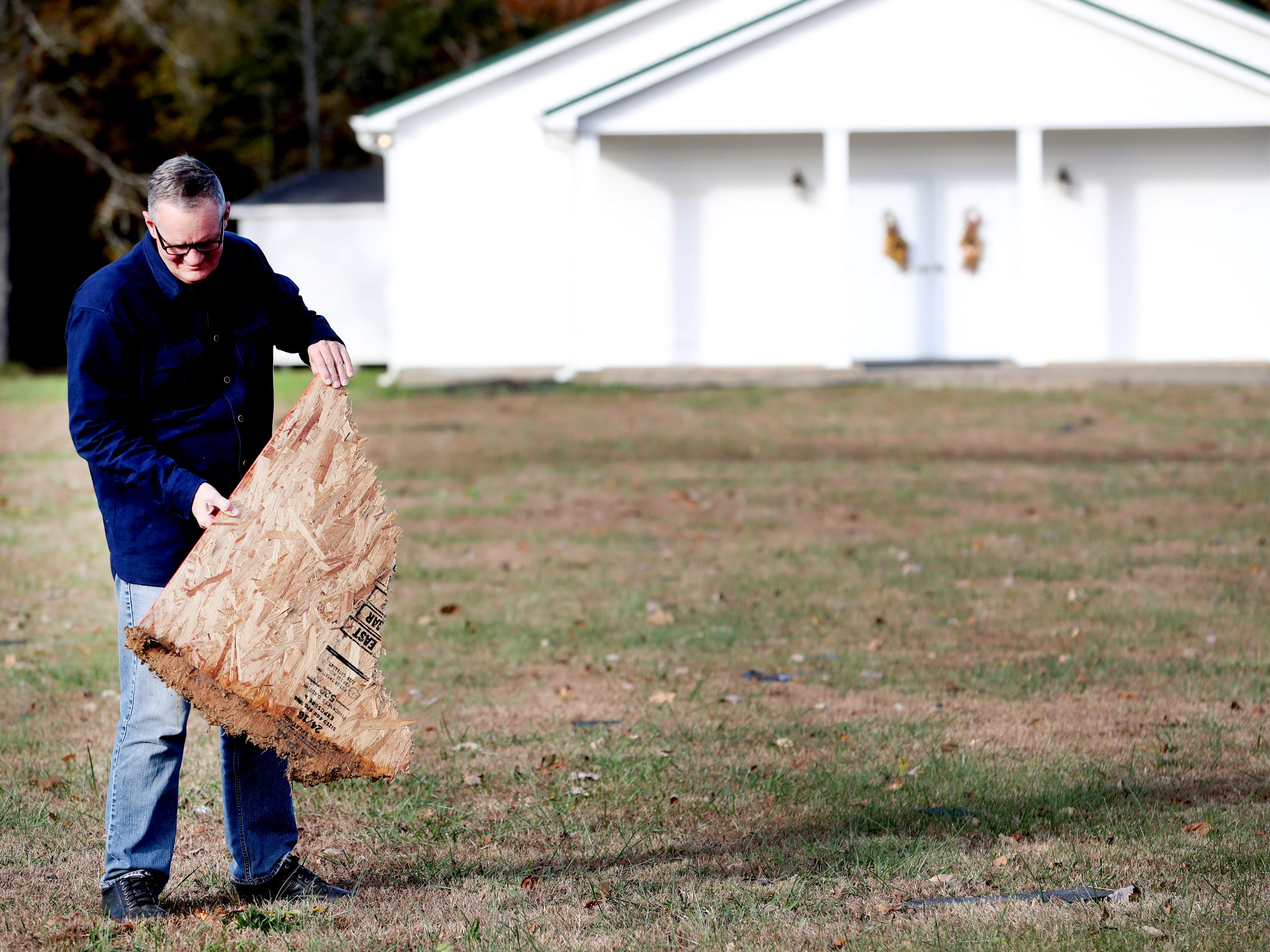 Billy Grimes Jr. pulls a piece of plywood out of the ground that was blown in the yard of the South Boros Pentecostals Church by a tornado that occurred  overnight, on Rock Springs Midland Road in Christiana, Tenn. on Tuesday, Nov. 6, 2018.