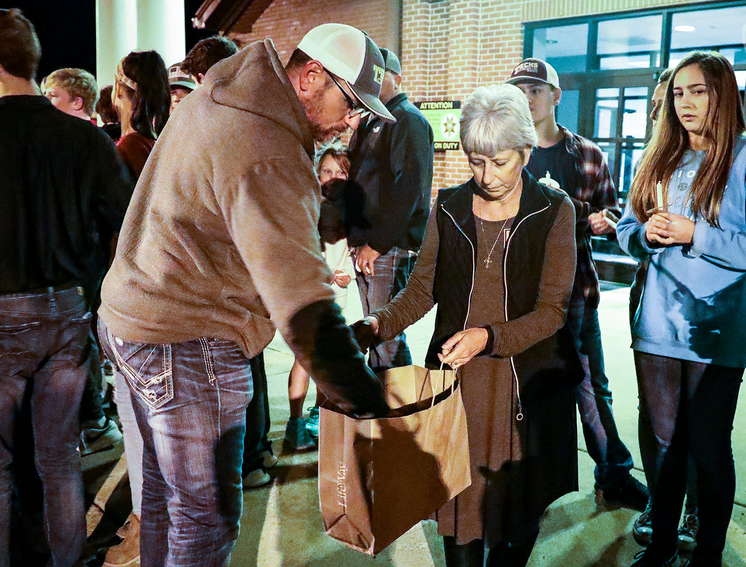 Matt Sledge takes a candle from Lauren Wiggins during a vigil in memory of Angie Walker held at Eagleville School. Walker, 41, was killed in and EF-2 tornado in Christiana, Tenn., on Tuesday, Nov. 6, 2018.