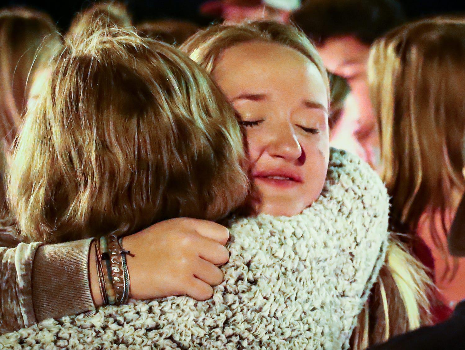 Olivia Walker, daughter of tornado victim Angie Walker, takes comfort in a hug during  a vigil at Eagleville School. Walker, 41, was killed in and EF-2 tornado in Christiana, Tenn., on Tuesday, Nov. 6, 2018.
