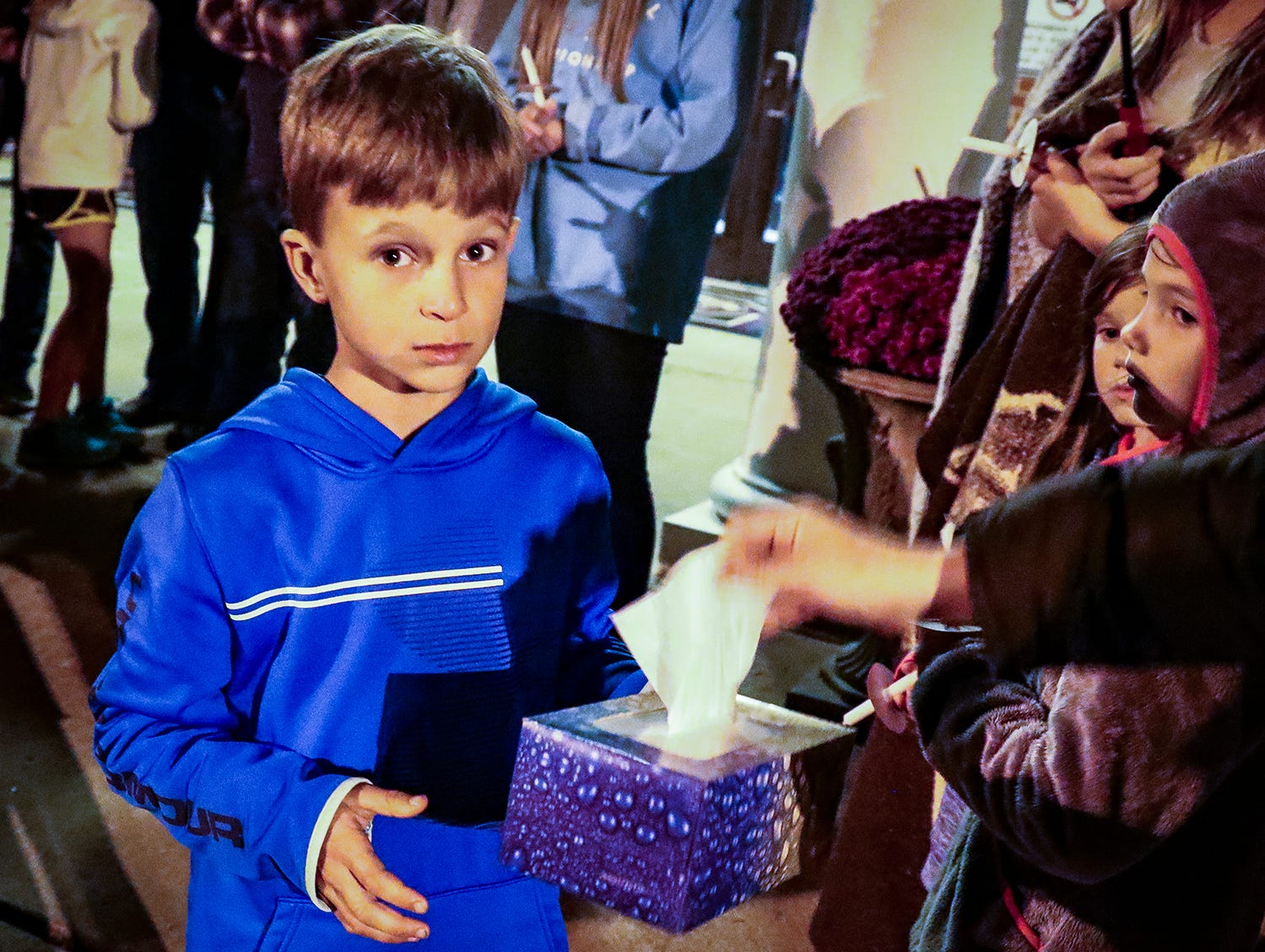 Benton Fox, a third-grader at Eagleville School, hands out tissues to the crowd gathered for a vigil in memory of Angie Walker. Walker, 41, was killed in and EF-2 tornado in Christiana, Tenn., on Tuesday, Nov. 6, 2018.