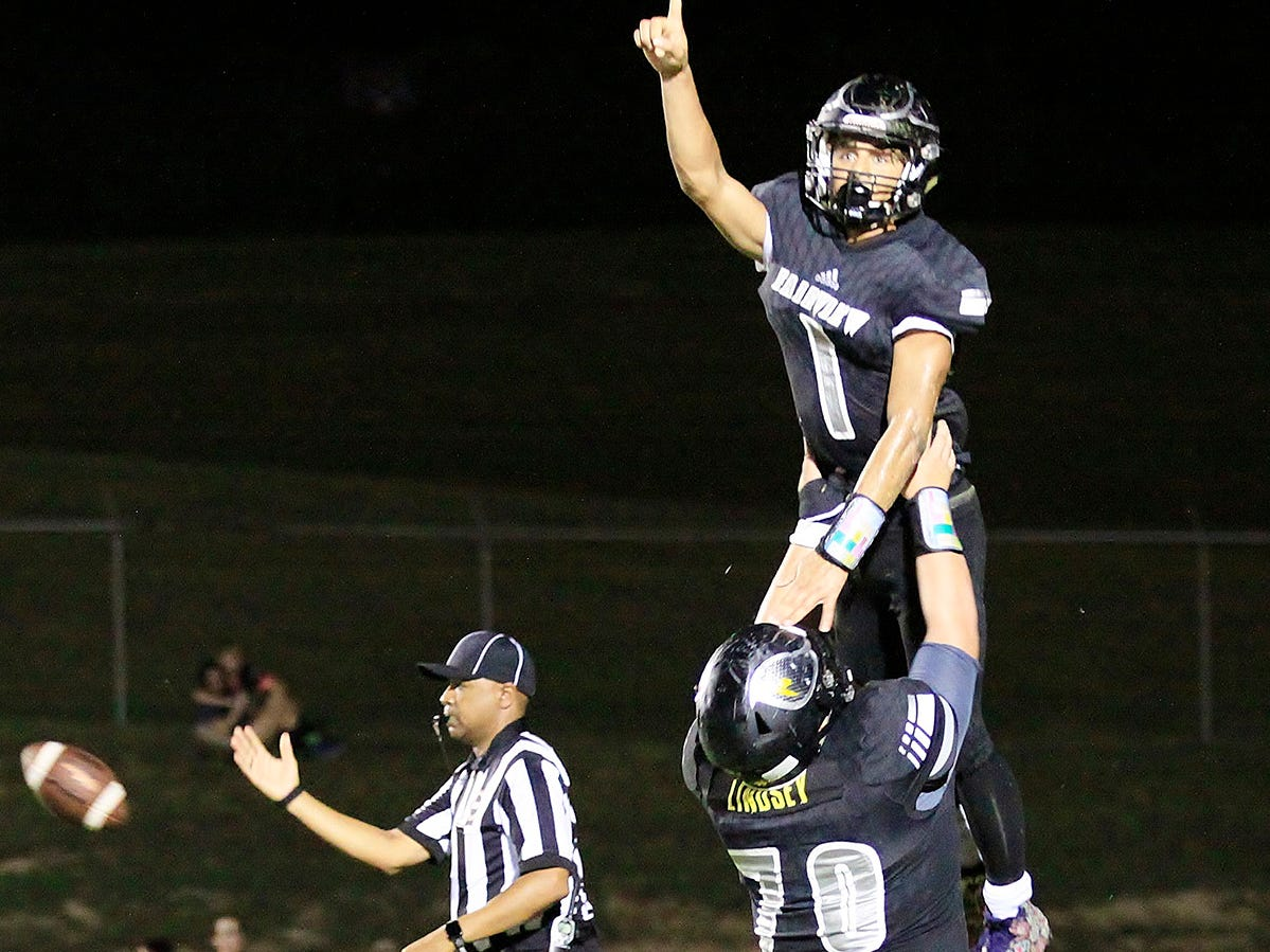 Jacket Kam Harris-Lusk celebrates his fourth touchdown with a high lift by teammate #70 Connor Lindsey in 49-42 win over Waverly September 7, 2018.
