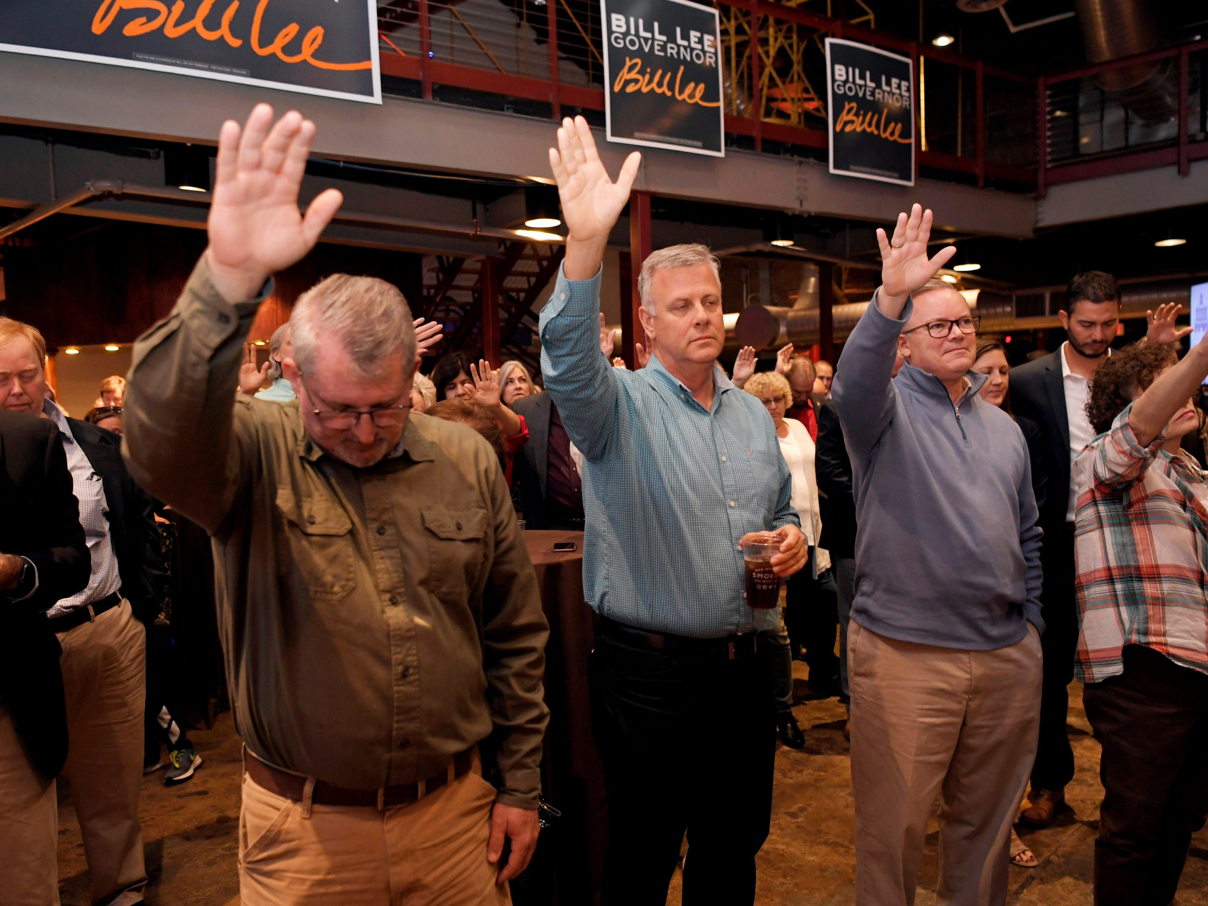 People lift their hands in prayer during the invocation at the election party for Republican gubernatorial candidate Bill Lee at the Factory in Franklin, Tenn. on Tuesday, Nov. 6, 2018.