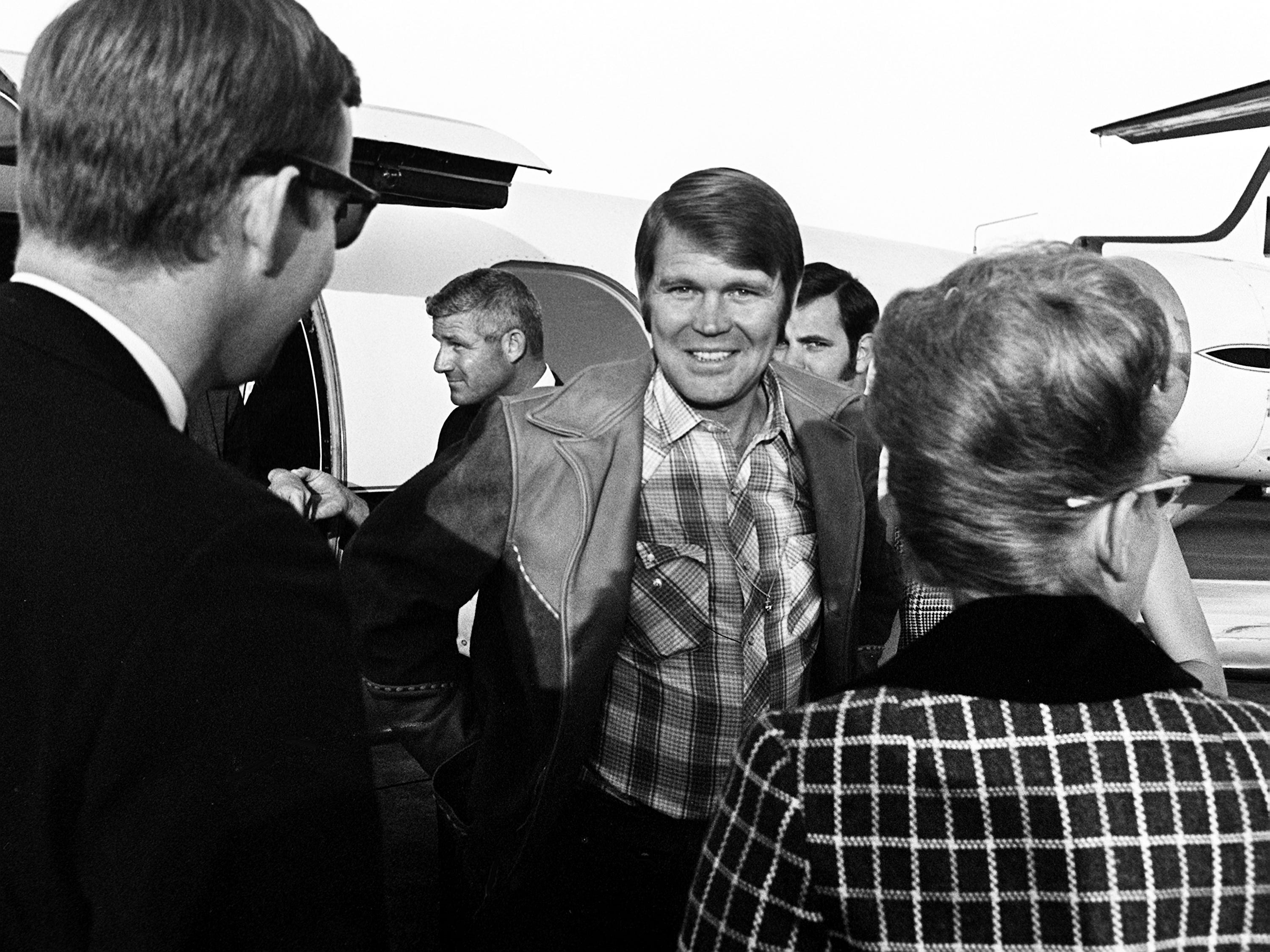 """Glen Campbell, center, is greeted after flying into town on a chartered Lear Jet provided by Kraft Foods and Capitol Records on Oct. 18, 1968, so he was able to just make the second annual CMA Awards show at the Ryman Auditorium. He was on location in Colorado where he is filming """"True Grit"""" with John Wayne."""