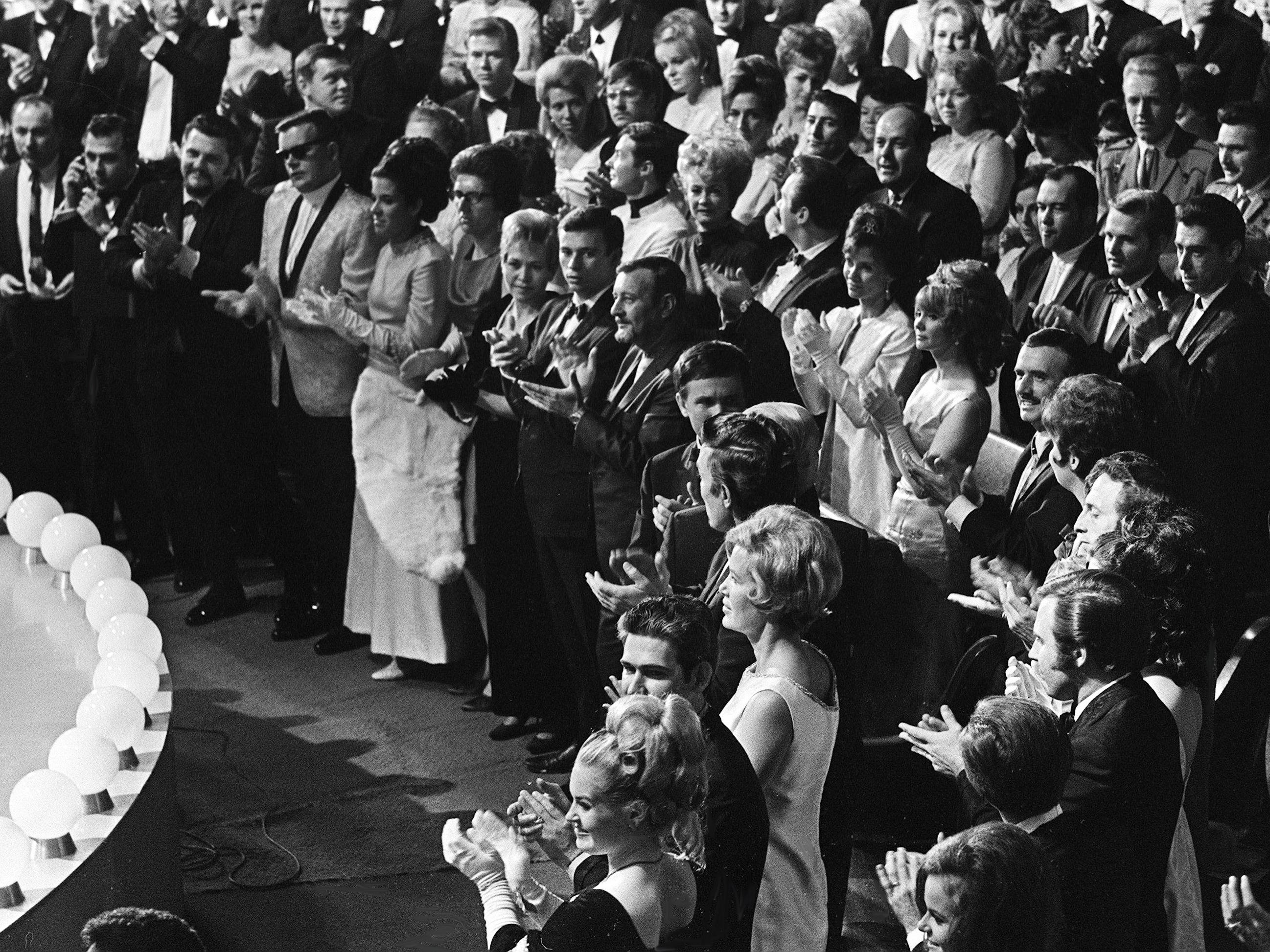 """The stars and fans stand as Bob Wills, writer of """"San Antonio Rose,"""" is named to the Country Music Hall of Fame during the second annual CMA Awards show at the Ryman Auditorium on Oct. 18, 1968."""