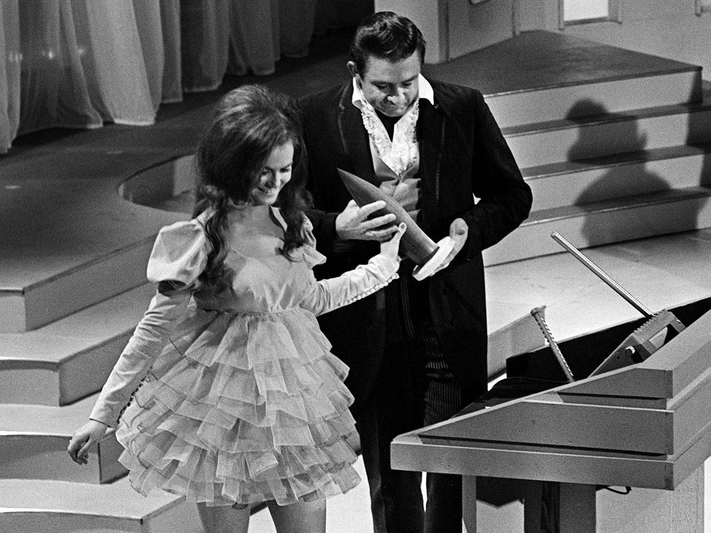 """Johnny Cash, right, receives his Best Album of the Year award from presenter Jeannie C. Riley during the second annual CMA Awards show at the Ryman Auditorium on Oct. 18, 1968. Cash won with his """"Folsom Prison Blues"""" album."""