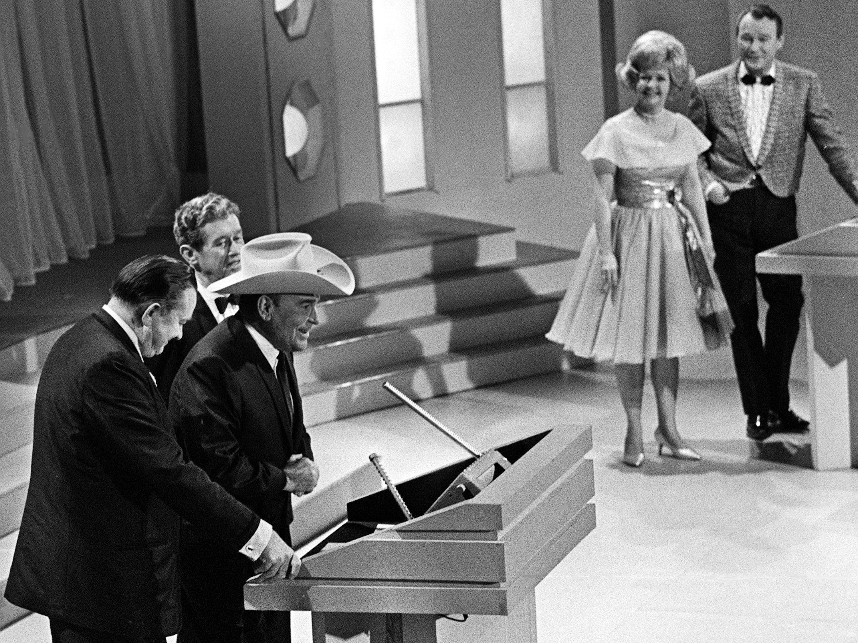 """""""Texas Playboy"""" Bob Wills speaks after being named to the Country Music Hall of Fame during the second annual CMA Awards show at the Ryman Auditorium on Oct. 18, 1968. Tex Ritter, left, and Roy Acuff made the presentation. In the background looking on are emcees Roy Rogers and Dale Evans."""