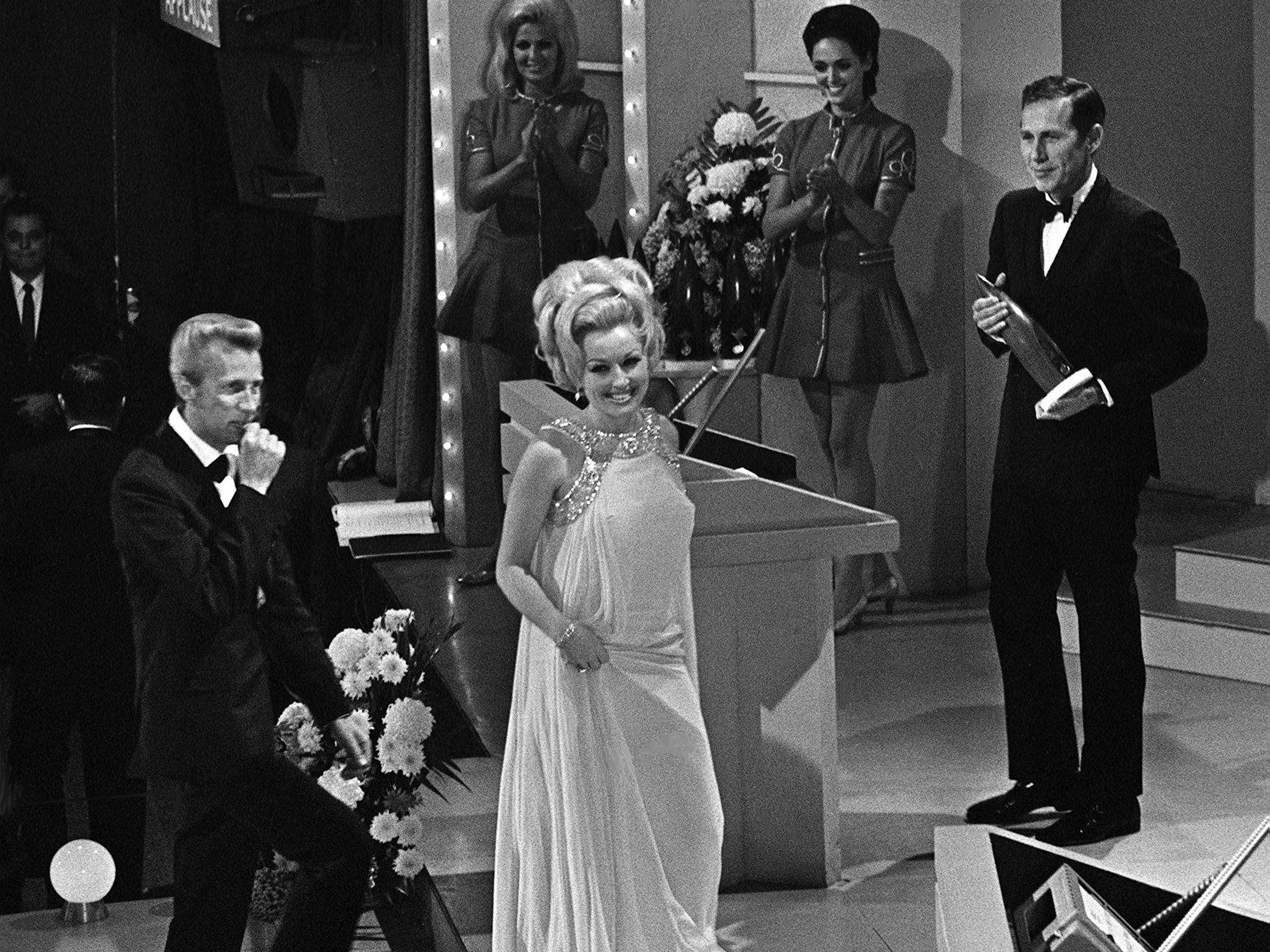 Porter Wagoner, left, and Dolly Parton walk on stage to accept their Vocal Group of the Year award during the second annual CMA Awards show at the Ryman Auditorium on Oct. 18, 1968. Presenter Chet Atkins, right, waits on the duo.