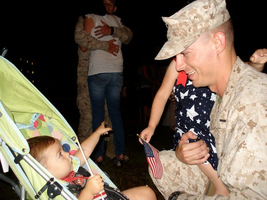 Aaron Dorn reunites with his children at Camp LeJeune in North Carolina after serving six months in Afghanistan in June 2011. Dorn is holding Abigail, then 3, and looking at Emilia, then 1, who is pointing at the bus he just stepped off.