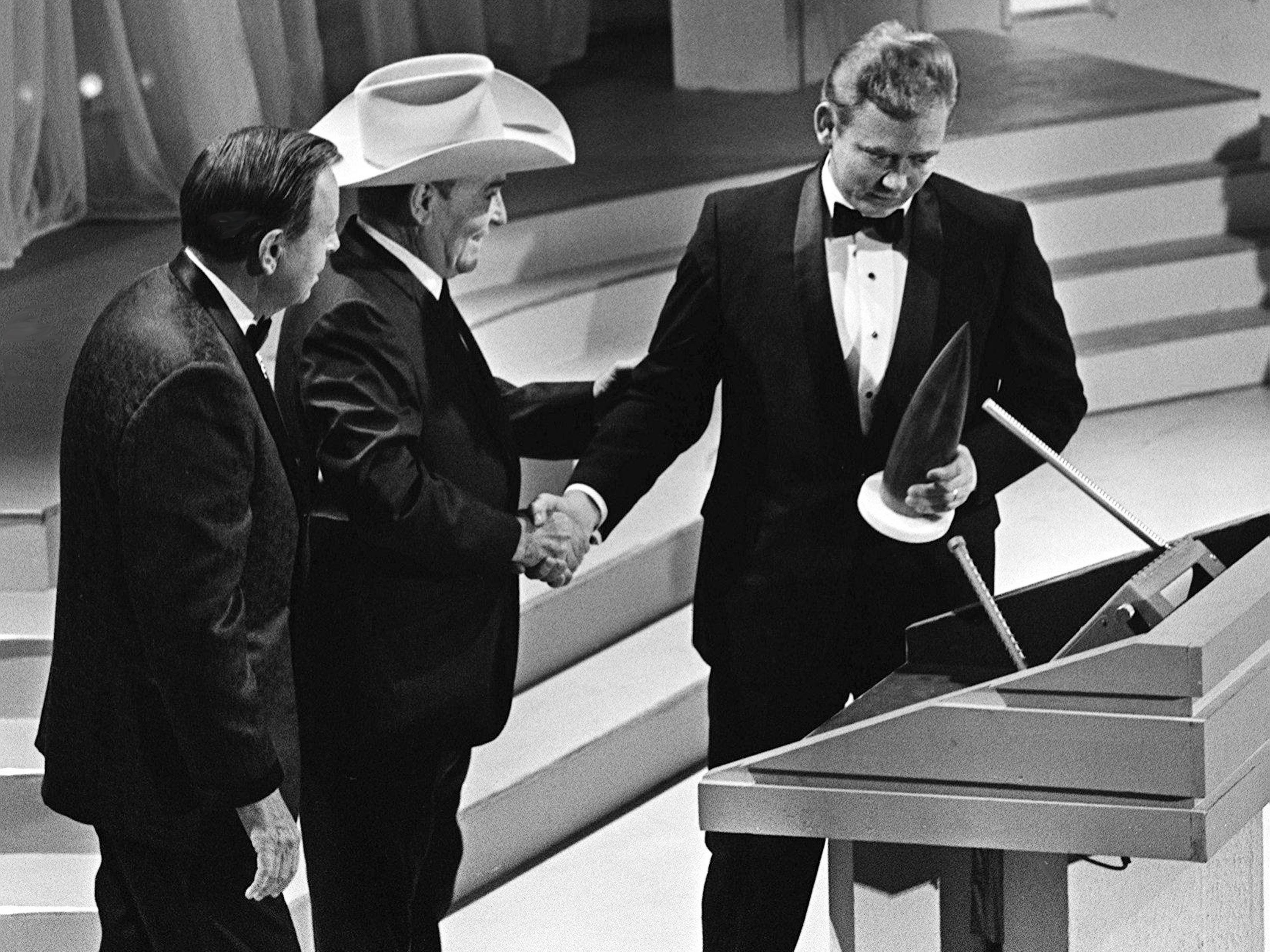 """Songwriter Bobby Russell, right, accepts his Song of the Year award from presenters Jimmie Davis and Bob Wills for """"Honey"""" during the second annual CMA Awards show at the Ryman Auditorium on Oct. 18, 1968."""