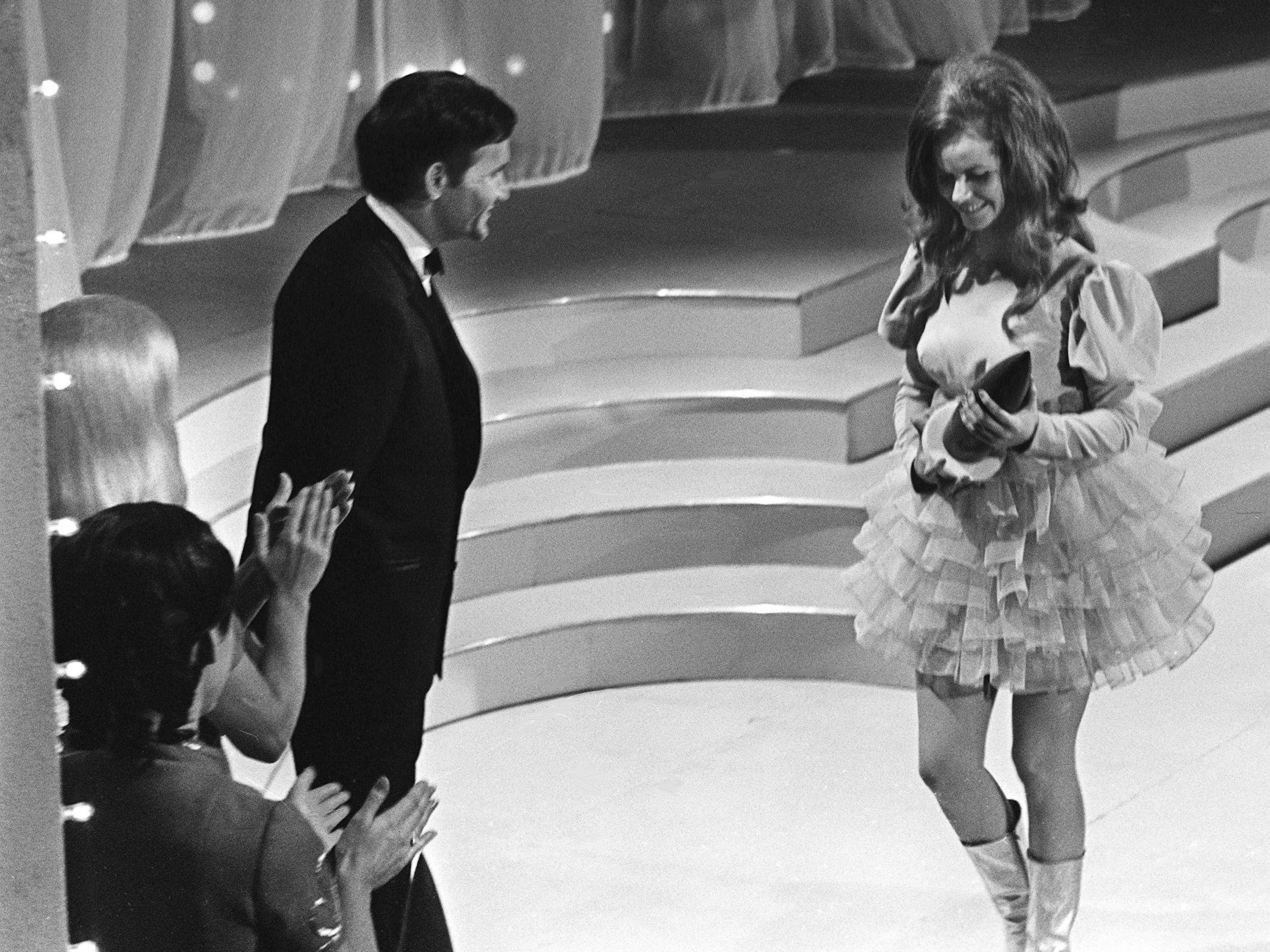 """Jeannie C. Riley, right, walks off the stage after accepting her Single of the Year award for """"Harper Valley PTA"""" as presenter Roger Miller looks on during the second annual CMA Awards show at the Ryman Auditorium on Oct. 18, 1968."""