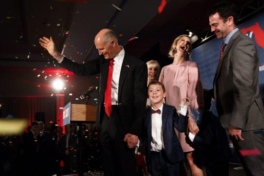 Gov. Rick Scott waves as he walks off stage with his family after declaring victory in his U.S. Senate race against Bill Nelson on Tuesday, Nov. 6, 2018, at LaPlaya Beach and Golf Resort in Naples.