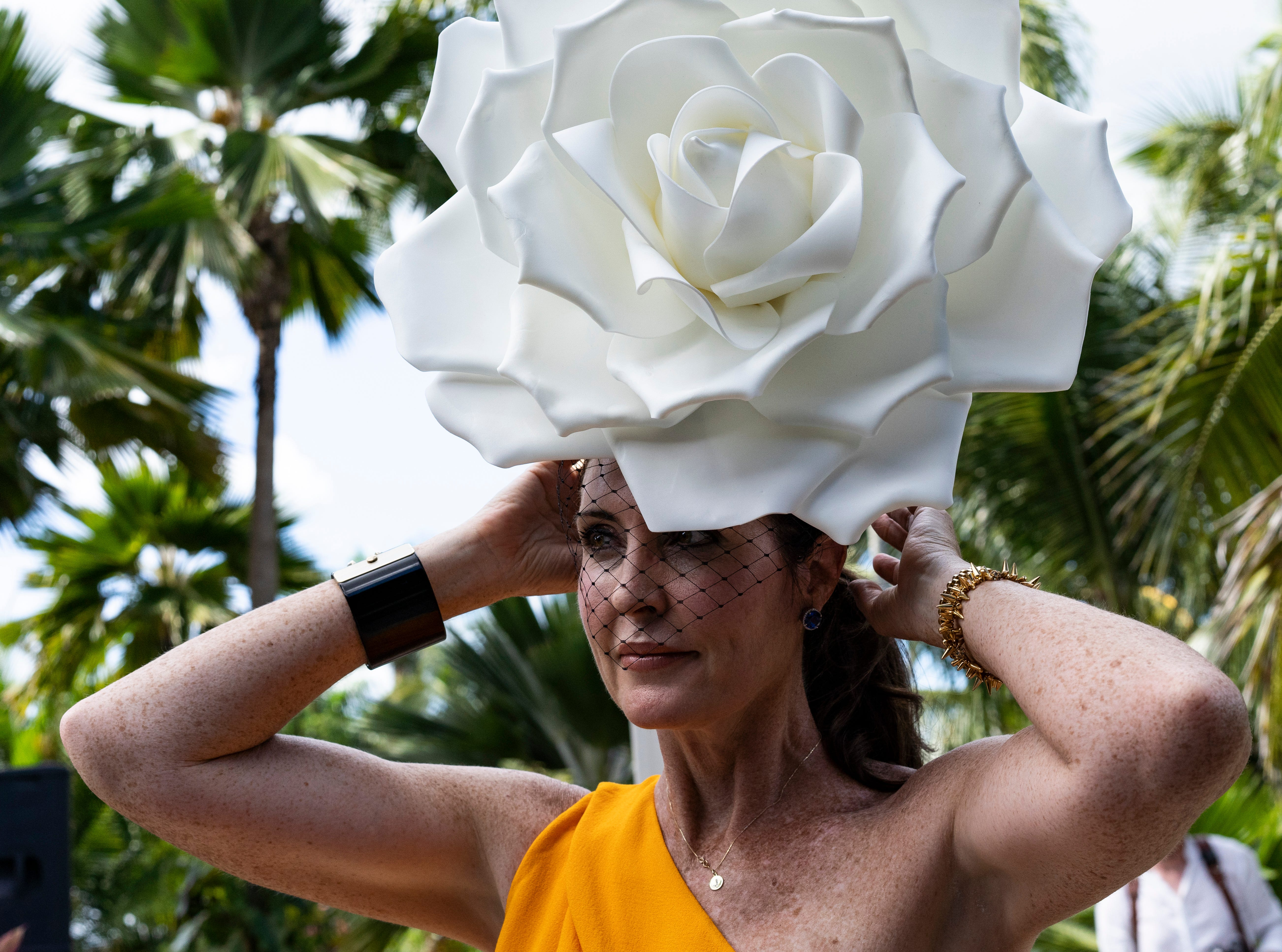 Denise Murray of Park Shore puts on her Aarturo Rios white rose hat on for 15th Annual Hats in the Garden fundraiser themed Rubies and Roses, at the Naples Botanical Garden on Nov. 7, 2018.