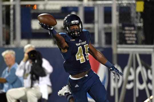 MIAMI, FL - SEPTEMBER 15:  FIU linebacker Rocky Jacques-Louis returns an interception 59 yards for a touchdown in the third quarter as the Golden Panthers defeated the University of Massachusetts Minutemen, 63-24, on Sept. 15 at Riccardo Silva Stadium in Miam.
