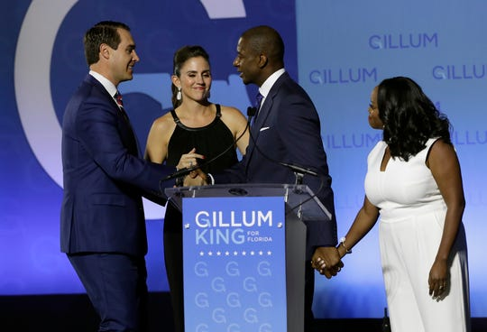 Florida Democratic gubernatorial candidate Andrew Gillum, second from right, shakes hands with running mate Chris King, left, as their wives Kristen King, second from left and R. Jai Gillum, right, look on after Gillum delivered his concession speech Tuesday, Nov. 6, 2018, in Tallahassee, Fla. Gillum lost to Republican former U.S. Rep. Ron DeSantis.