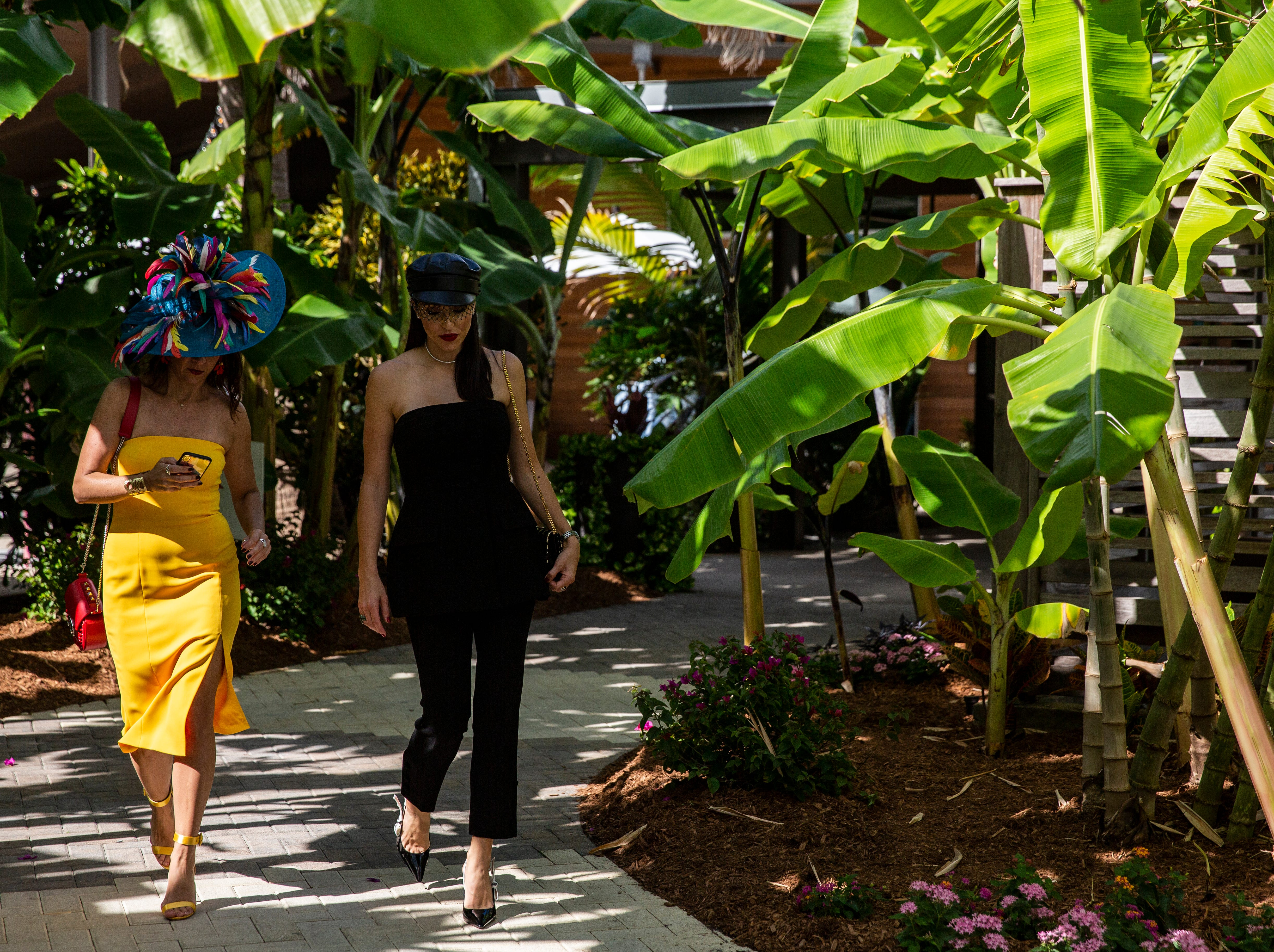 Jennifer Parisi, left and Ashley Gerry, right, from Naples, walk to the Hats in the Garden luncheon at Naples Botanical Garden on Nov. 7, 2018.