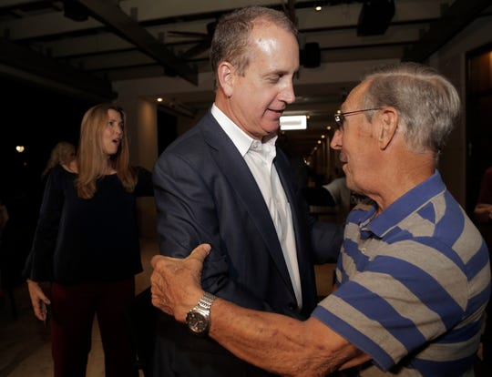 Congressman Mario Diaz-Balart, center, is greeted by a supporter during a victory party at the Flamingo Terrace at Hialeah Park, Tuesday, Nov. 6, 2018, in Hialeah.