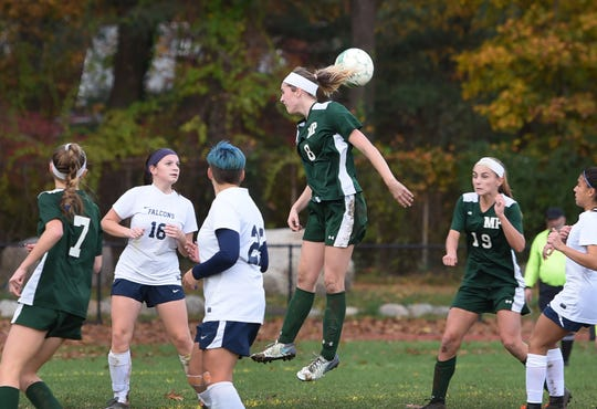 Avery O'Dell (no. 8) of Midland Park (in green) heads the ball during the North 1, Group 1 girls soccer semifinal at Midland Park High School on 11/07/18. Midland Park won the game 6 to 1.