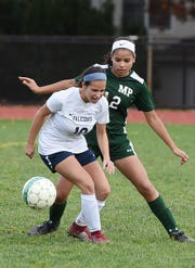 Alyssa Genao (no. 12) of Midland Park (in green) pressures as Ashley Georgevich (no. 10) of Saddle Brook (in white) tries to control the ball during the North 1, Group 1 girls soccer semifinal at Midland Park High School on 11/07/18. Midland Park won the game 6 to 1.