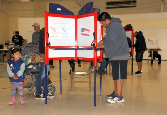 Ricky Baca selected his candidates in voting booth at Holy Family Parish Center, as a child looks on from another booth.