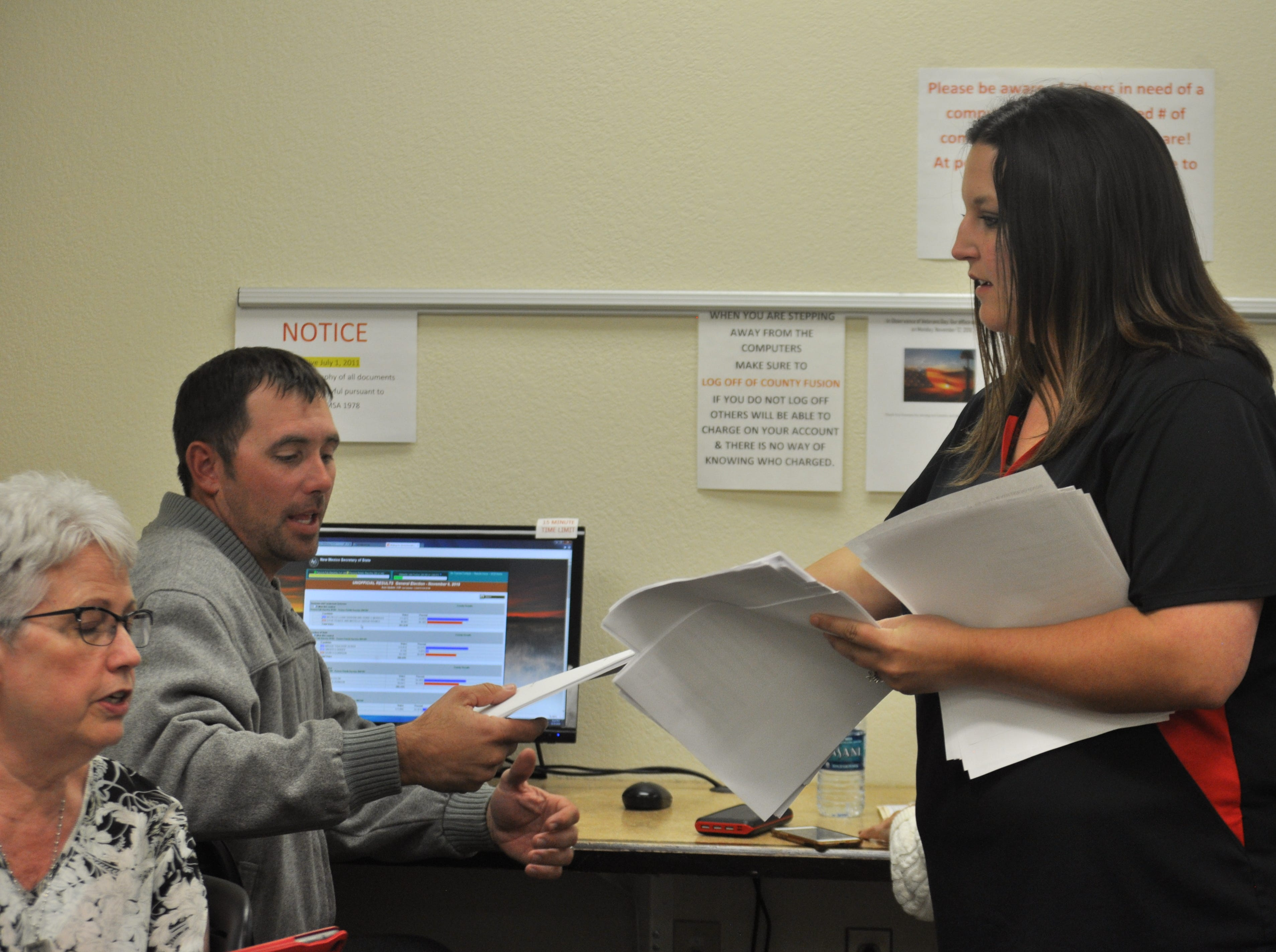 Amy Tarvin Brewer hands copies of results from seven precincts and early voting to Steven McCutcheon, candidate for the Eddy County Board of Commissioners, Oct. 6  at the Eddy County Clerk's Office.