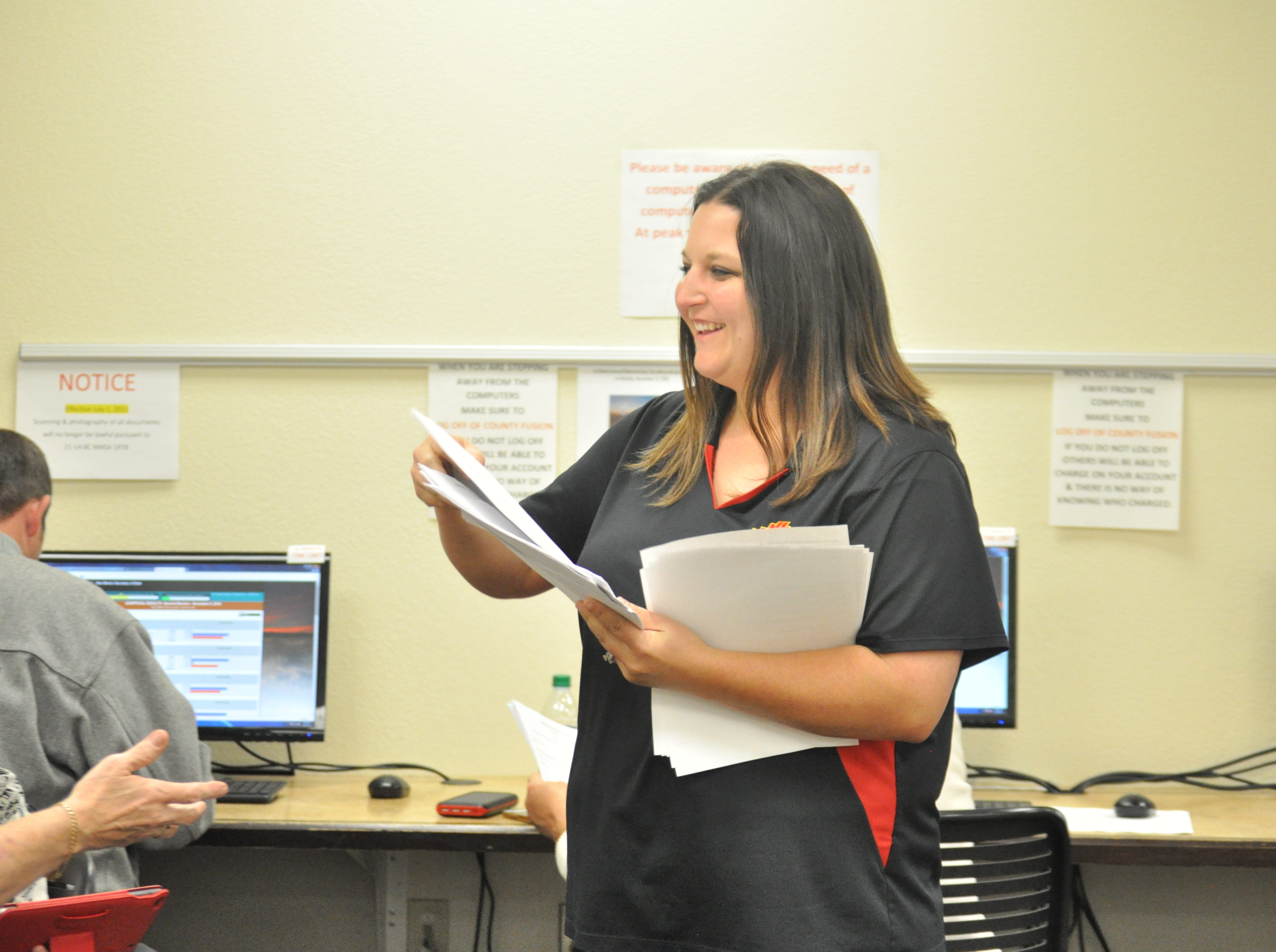 Amy Tarvin Brewer passes out copies of early voting numbers Oct. 6 at the Eddy County Clerk's Office.