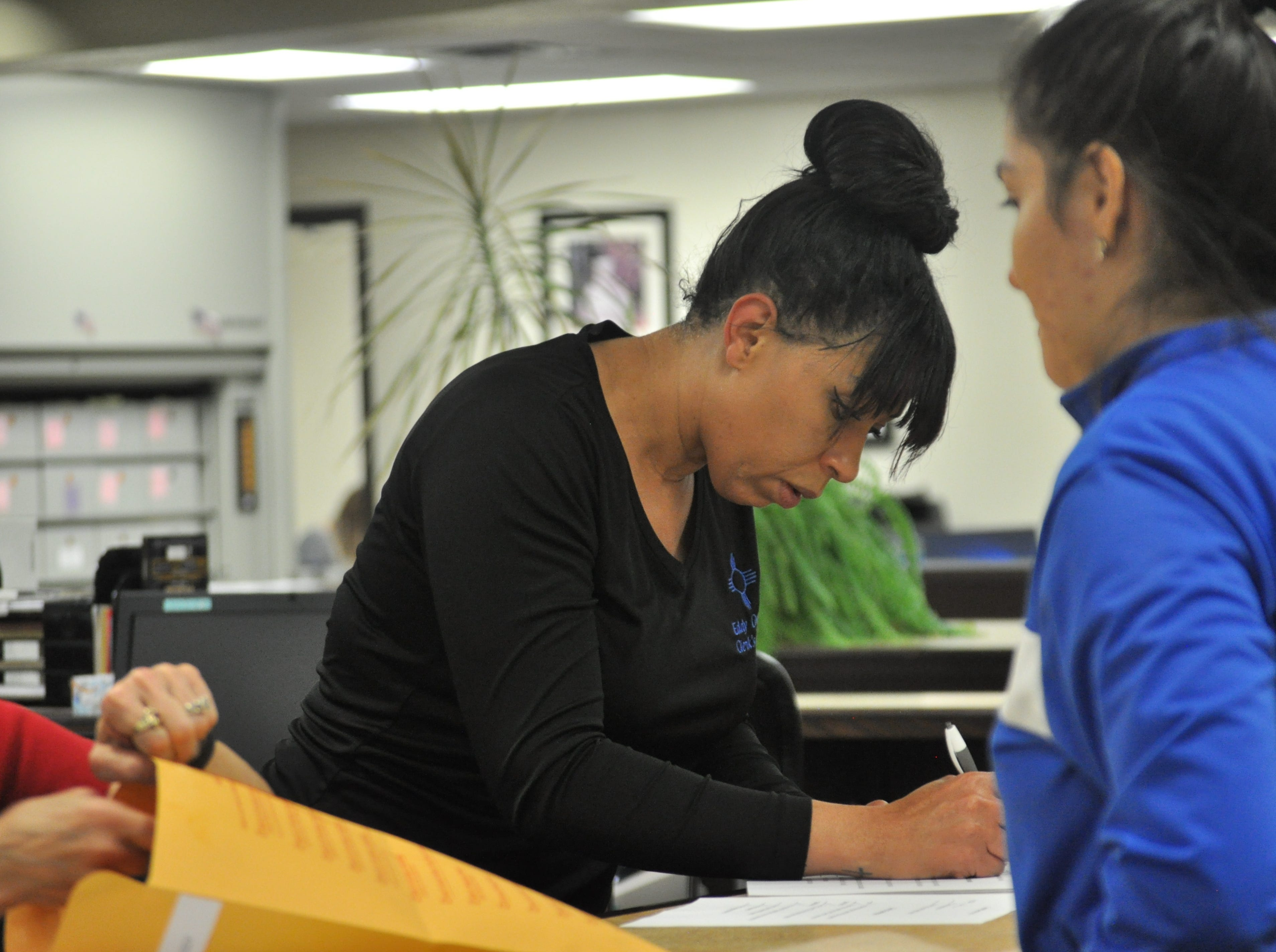 An employee of the Eddy County Bureau of Elections receives paperwork from a poll worker Oct. 6 following the close of polling locations in the general election.
