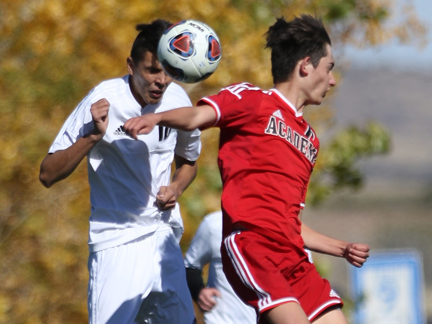 Aztec's Karson Adcock head bumps the ball away from Albuquerque Academy's Neven Zapatka during Wednesday's 4A state quarterfinals in Bernalillo.