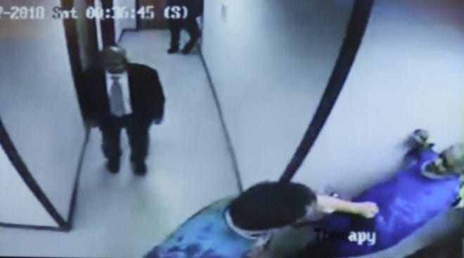 A March 17 video still from inside a Livonia psychiatric clinic shows an attendant, lower right, raise his fist as if to strike patient Paul Bagozzi as Dr. Hanumaiah Bandla, left, walks in on the scene from an adjacent hallway. Bagozzi was not punched in this particular struggle.
