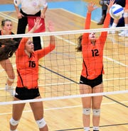 Northville's Laryssa Imbuzerio (16) and Jenna Boksha (12) team up on the front row for the block.