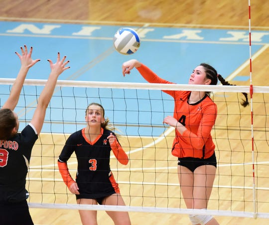 Northville's Michael VanAcker (4) goes up for the attack in front of teammate Hannah Grant.