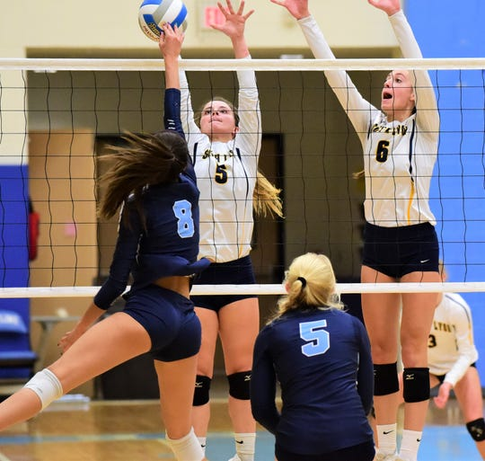 South Lyon's Emily Kalinowski (5) and Abby Durecki (6) go up for the block against Skyline's Kendall Murray (8).