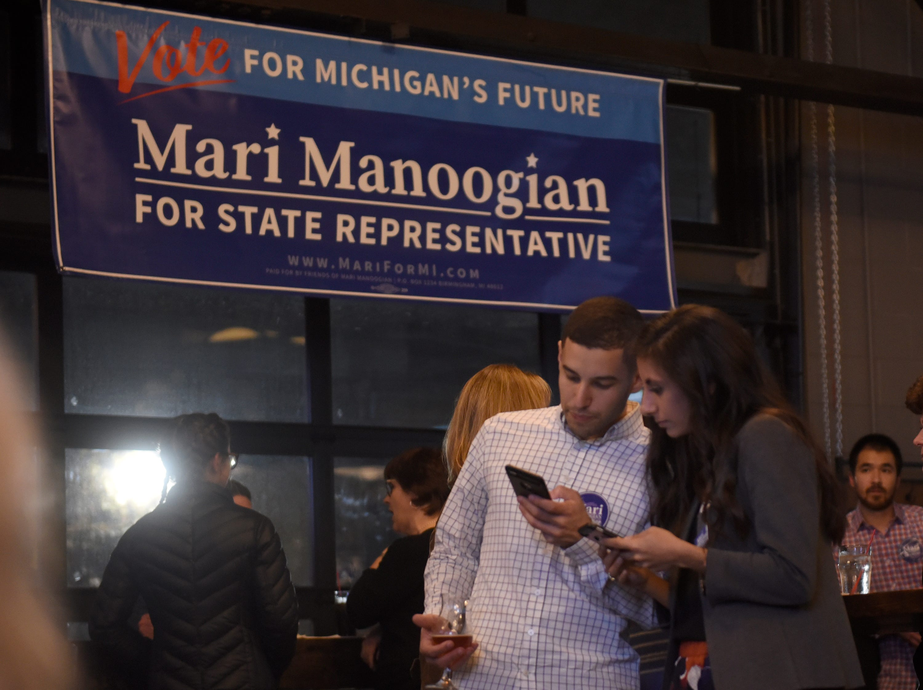 State House District 40 candidate Mari Manoogian looks at results with boyfriend Drew Parks at her election party at Dick O'Dow's Nov. 6, 2018.