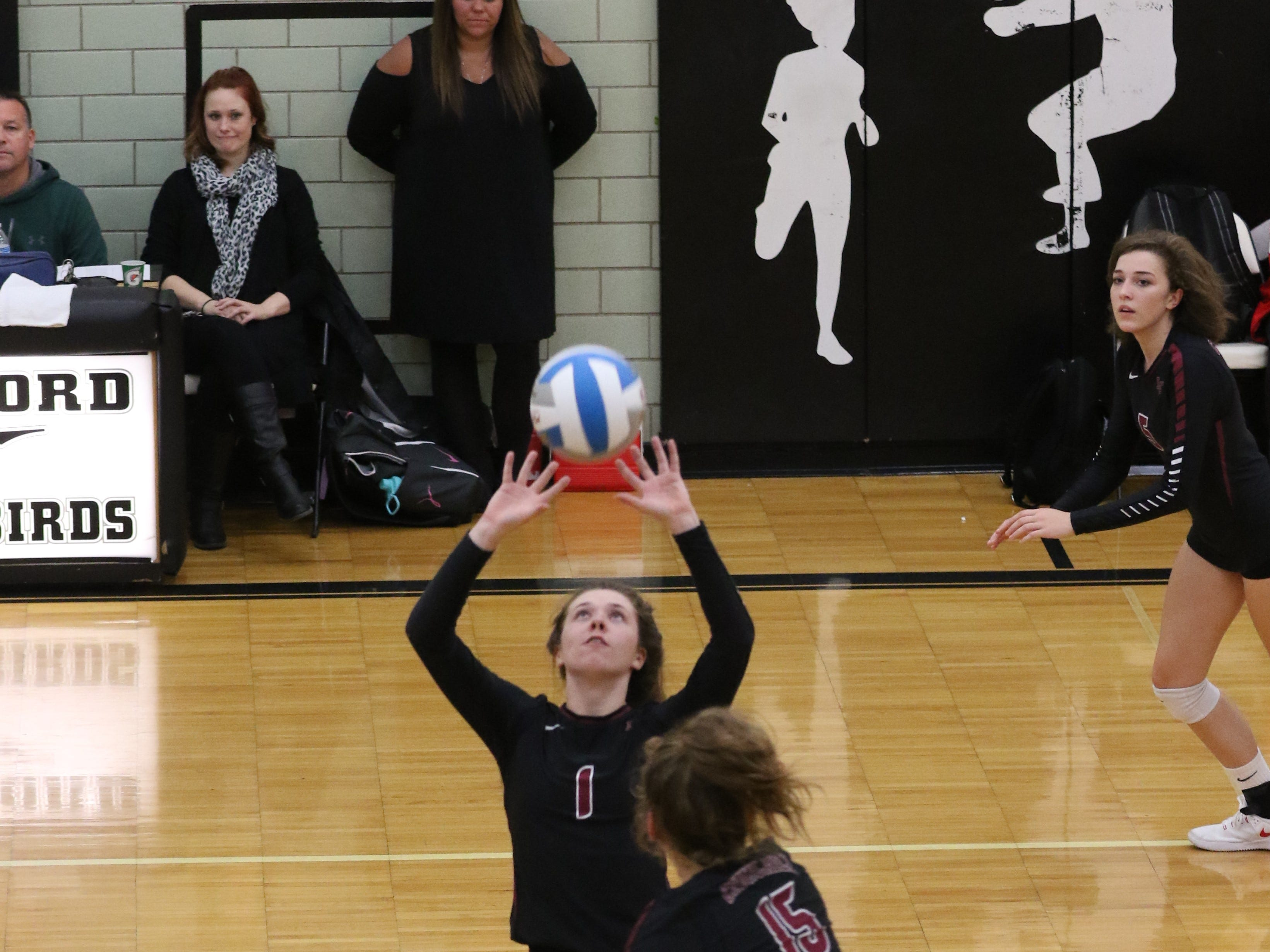 Chargers' senior setter Grace Vaeth (1) puts the ball on a tee for senior middle hitter Summer Clark. In the foreground is junior outside hitter Sarah Dunn (13).