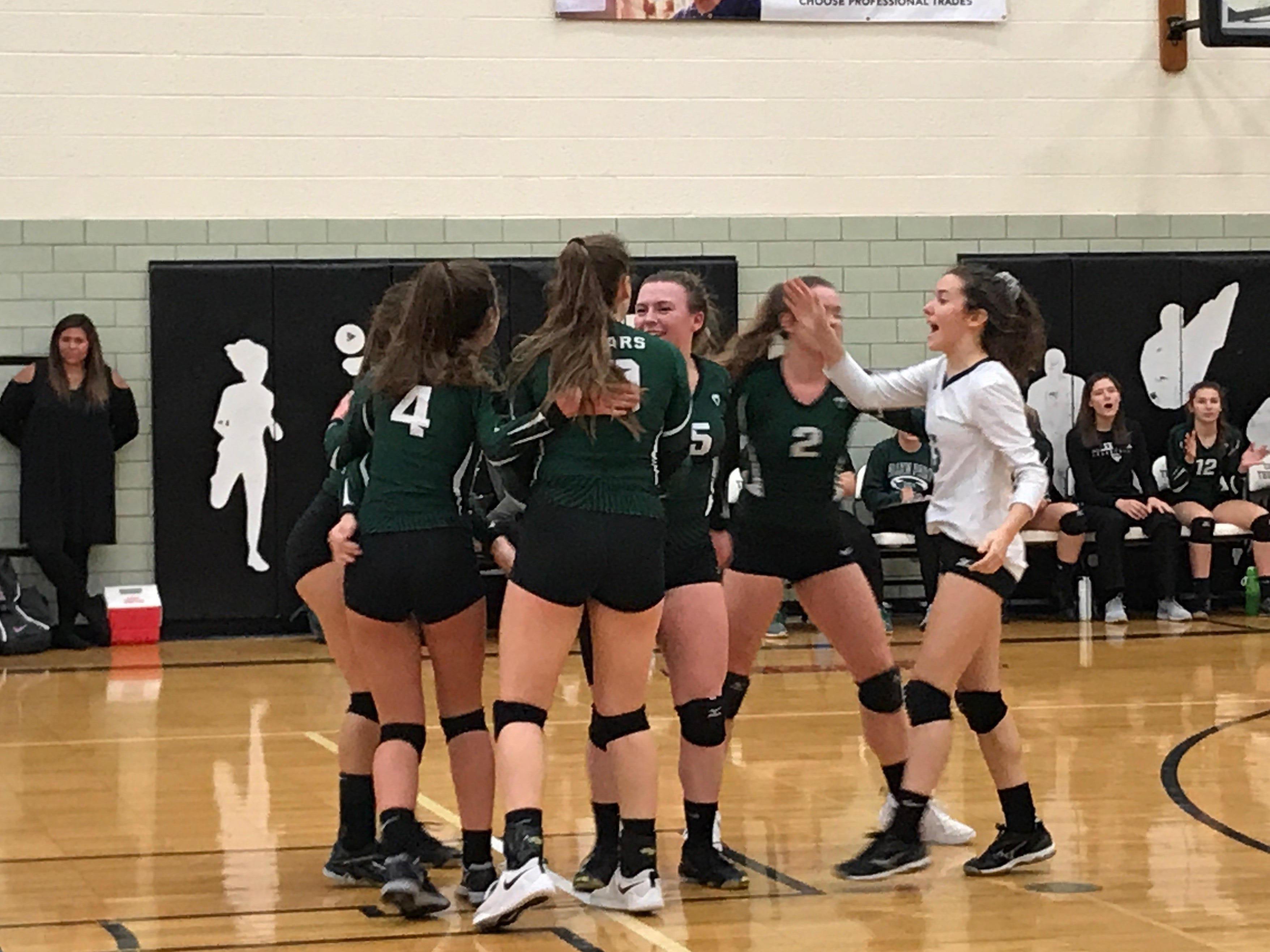 Allen Park volleyball players congratulate each other after scoring a point. Despite not being able to win a set against Livonia Churchill, the Jaguars had stretches of very competitive play during the Division 1 regional semifinal.