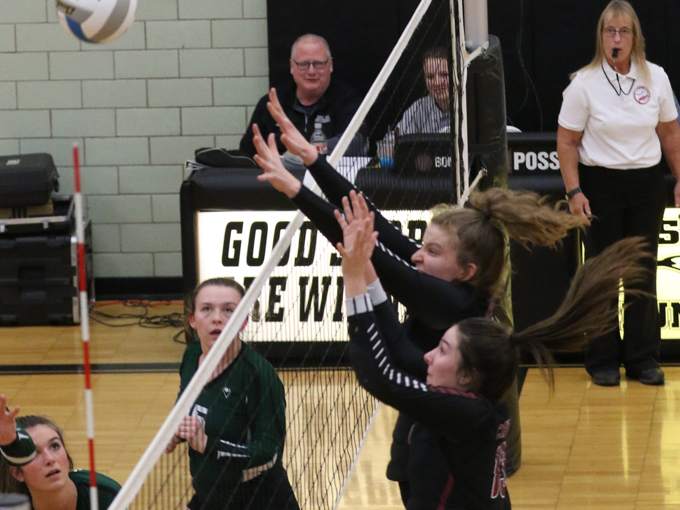 Jumping up in unison at the net are Livonia Churchill's Mary Claire Yost (foreground) and Summer Clark.