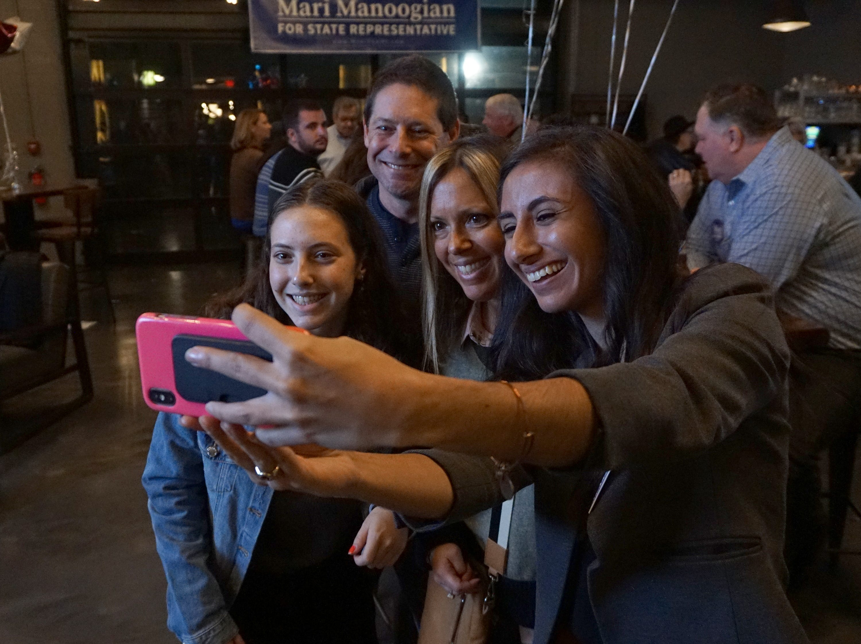 The Kroll family - Lilley (left), Todd and Jennifer take a selfie with state House District 40 candidate Mari Manoogian at Dick O'Dow's in Birmingham during election night party Nov. 6, 2018.