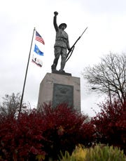 A statue depicting a World War I doughboy stands on South Memorial Drive in Appleton at the foot of a flag marking 100 years since the end of the Great War on Nov. 11, 1918.