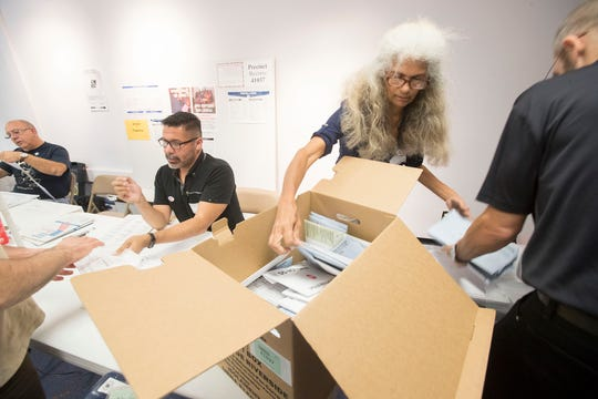 A volunteer empties out a provisional ballot box at precinct number 41031 in Palm Springs during the 2018 midterm elections.