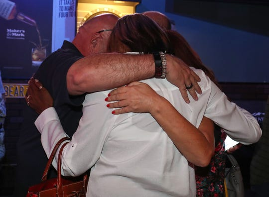 Scott Matas, Gary Gardner and Jan Pye embrace before the first election results came in the Desert Hot Springs City Council race, November 6, 2018.