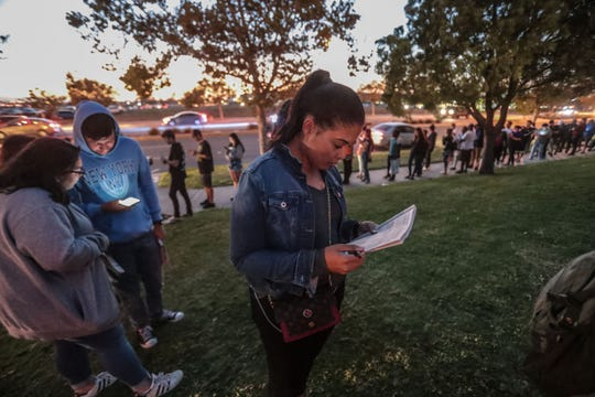 Mika Gipson, 28, of Corona studies a voter guide as she waits to vote in a line that wraps around one of the buildings at the County of Riverside Registrar of Voters in Riverside on Tuesday, November 6, 2018.