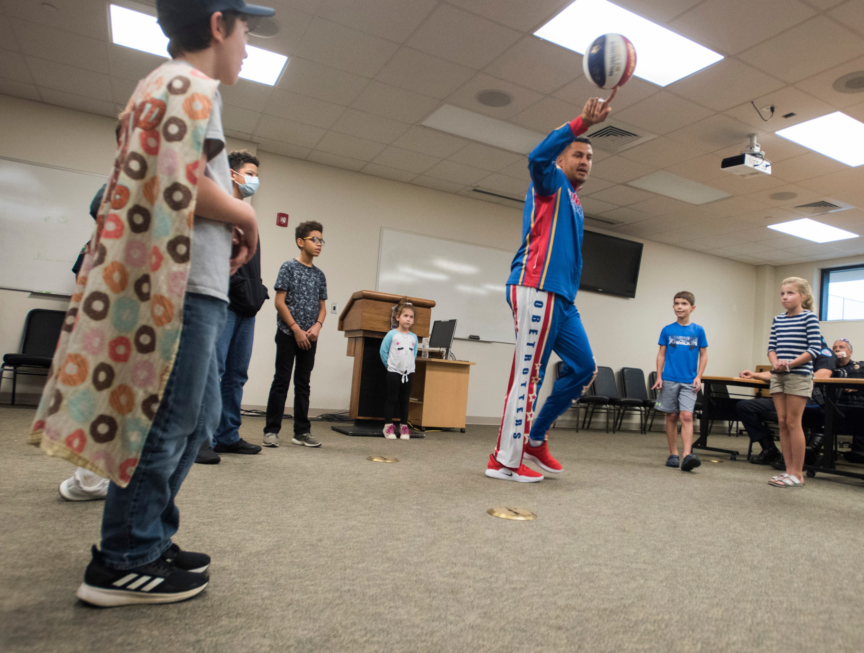 "El Gato Melendez, a member of the Harlem Globetrotters, performs a few tricks as Tyler Carach, left, and a group of children looks on during a birthday party for the 11-year old at the Pensacola Police Dept. on Wednesday, Nov. 7, 2018. Carach is also known as the ""donut boy"" and has delivered more than 70,000 of the pastries to law enforcement officers around the country."