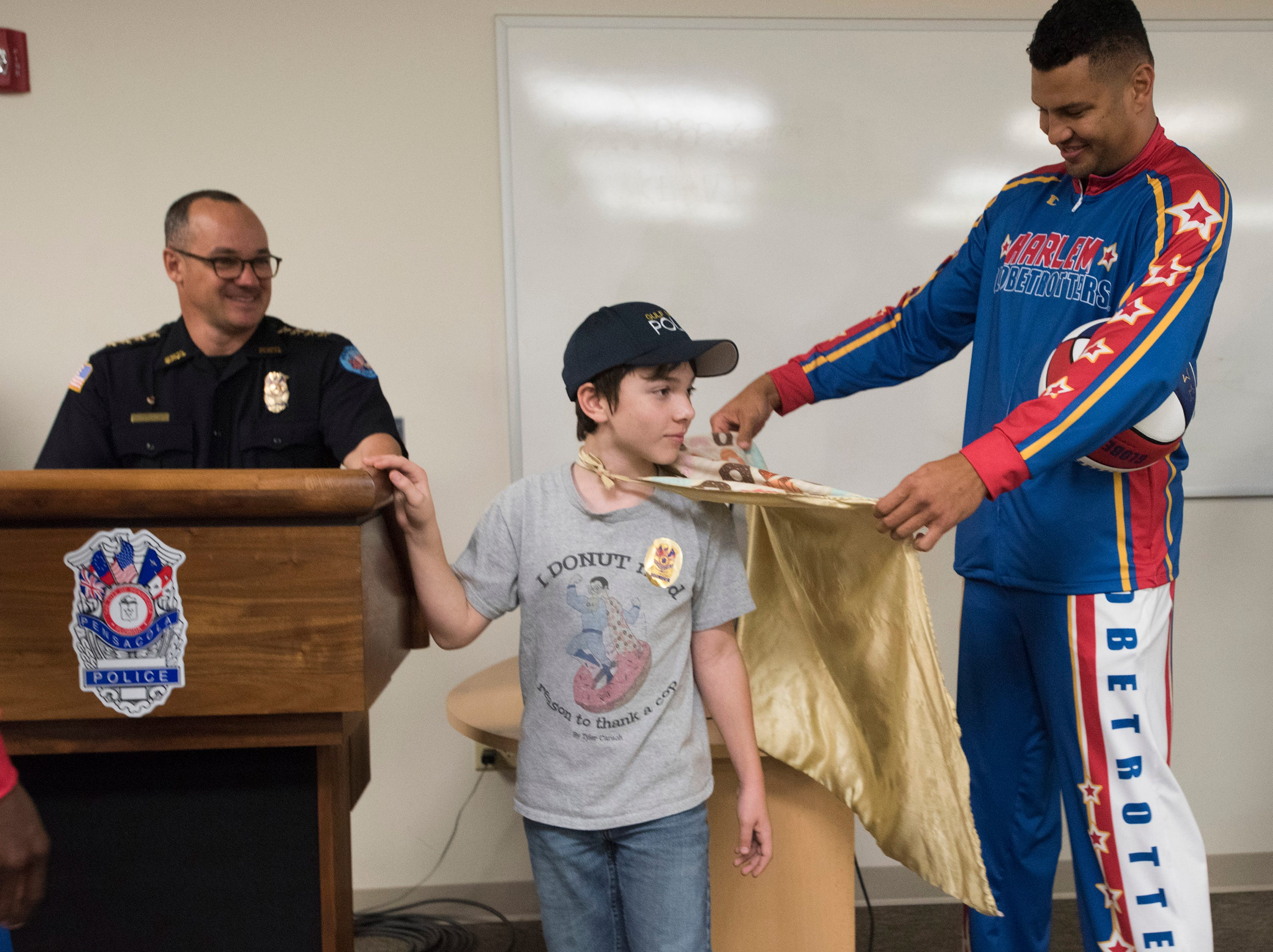 "El Gato Melendez, a member of the Harlem Globetrotters, checks out Tyler Carach's outfit during a birthday party for the 11-year old at the Pensacola Police Dept. on Wednesday, Nov. 7, 2018, while Chief Tommi Lyter looks on.  Carach is also known as the ""donut boy"" and has delivered more than 70,000 of the pastries to law enforcement officers around the country."