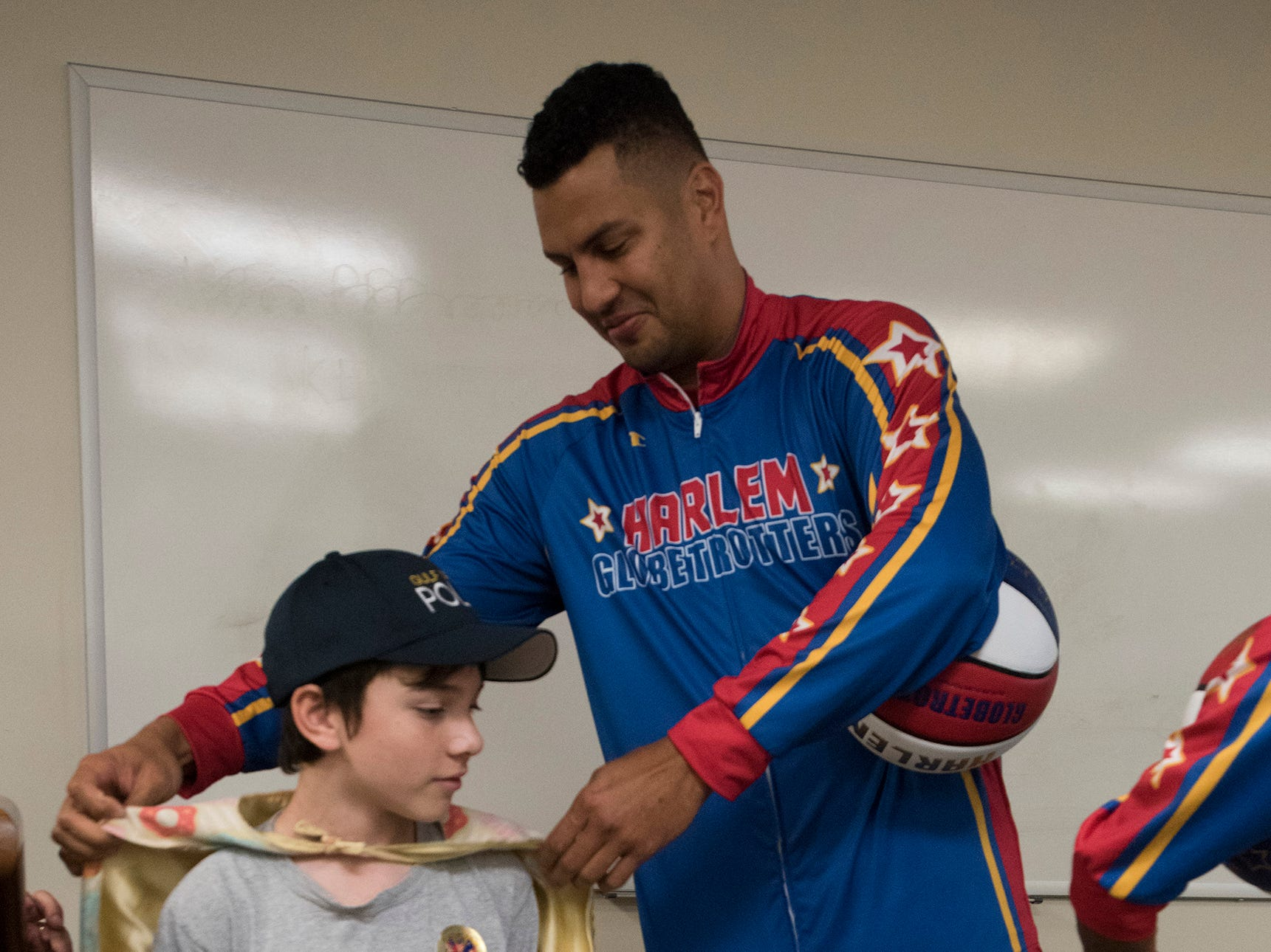 "El Gato Melendez, a member of the Harlem Globetrotters, checks out Tyler Carach's outfit during a birthday party for the 11-year old at the Pensacola Police Dept. on Wednesday, Nov. 7, 2018. Carach is also known as the ""donut boy"" and has delivered more than 70,000 of the pastries to law enforcement officers around the country."
